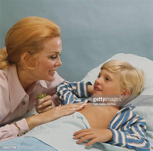 Mère appliquant même de grosses fausses notes-on enfant souriant sur la poitrine,