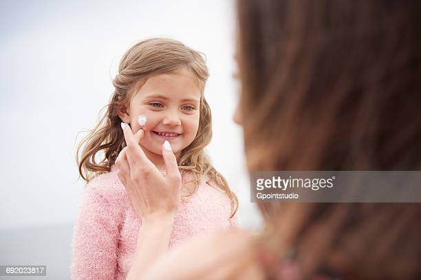 Mother applying sun cream on daughters cheek