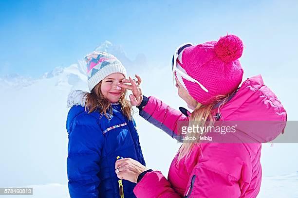 Mother applying sun cream on daughters face, Chamonix, France