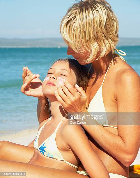 mother applying sun cream to daughter's (8-10) face on beach - girls sunbathing stock photos and pictures