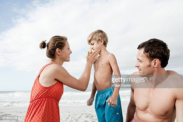 Mother applying sun cream to son