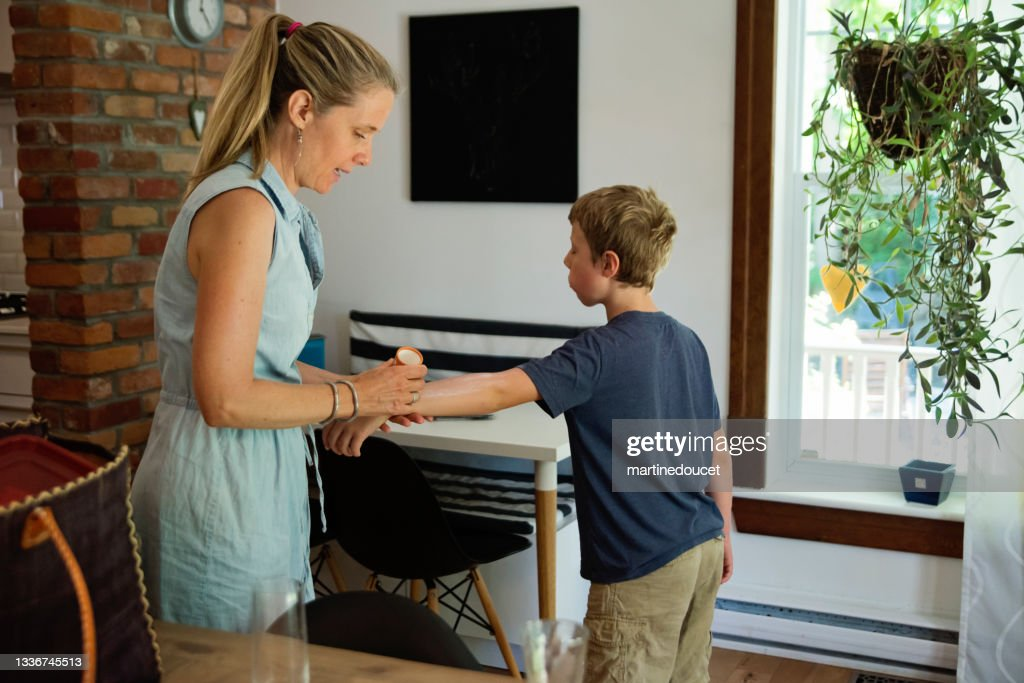 Mother applying sun protection on son's arms before going out. : Stock Photo