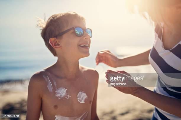 mother applying sunscreen to son - sunscreen stock photos and pictures
