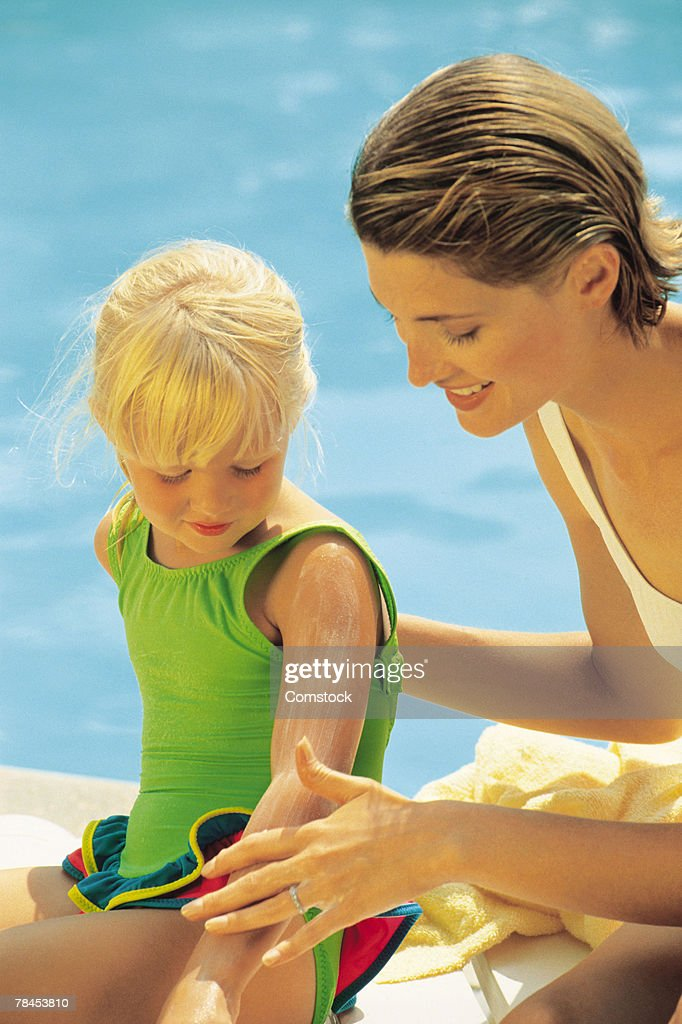 Mother applying suntan lotion to child sitting by pool : Stockfoto