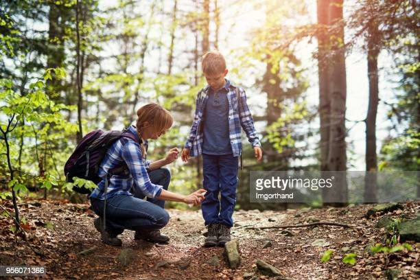 mother applying tick repellent on son - insect stock pictures, royalty-free photos & images