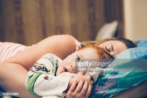 Mother asleep with child awake