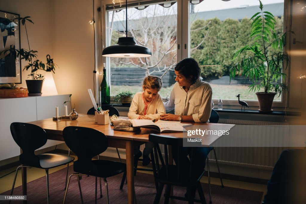 Mother assisting daughter in writing homework while sitting at home : Stock Photo