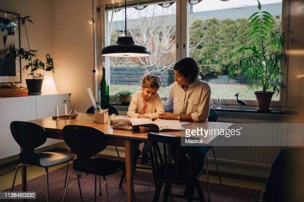 mother assisting daughter in writing homework while sitting at home - residential building stock pictures, royalty-free photos & images