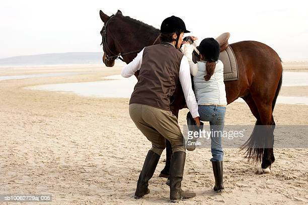 Mother assisting daughter (6-7) to mount horse on beach
