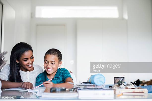 mother assisting son in doing homework - homeschool stock photos and pictures
