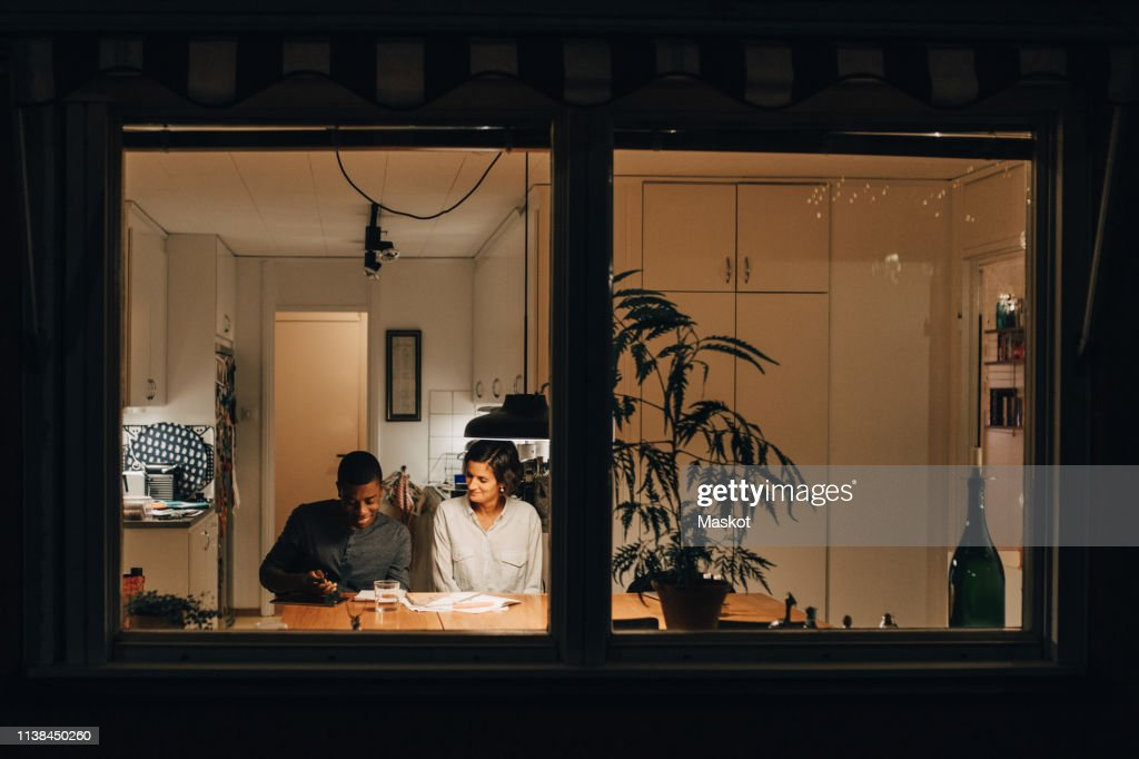 Mother assisting son in studying at home seen through window : Stockfoto
