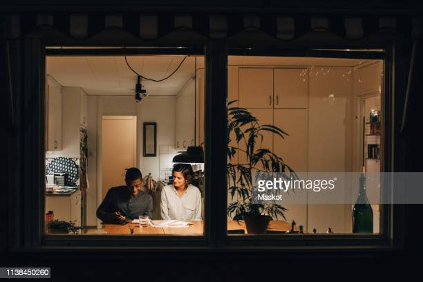 mother assisting son in studying at home seen through window - huis stockfoto's en -beelden