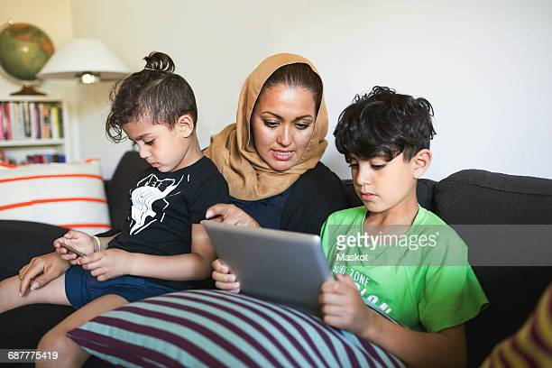 Mother assisting son in using digital tablet while sitting on sofa at home