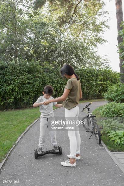 mother assisting son in using self-balancing board on road against plants - hoverboard stockfoto's en -beelden
