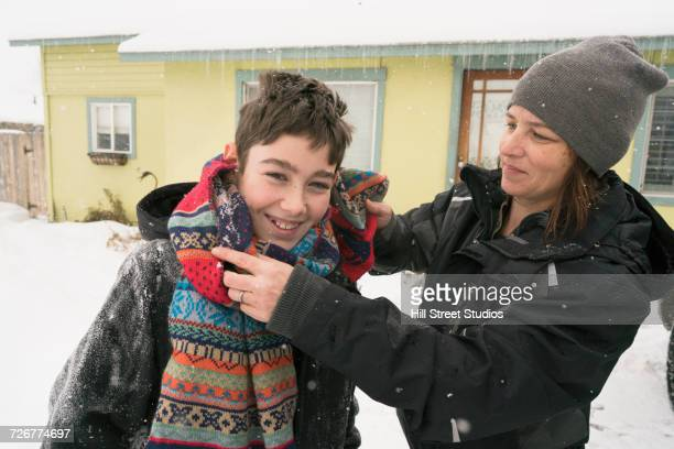 Mother assisting son with scarf in snow