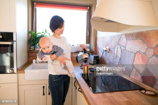 Mother at home holding baby son in her arms, preparing coffee