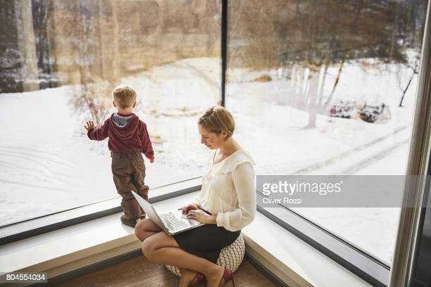 mother at home using laptop with son looking out of the window - frau bluse durchsichtig stock-fotos und bilder