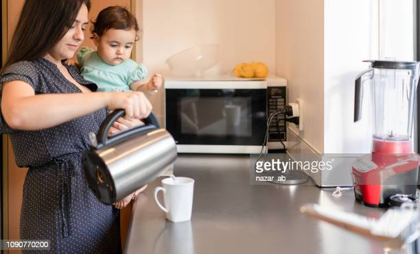 Mother at home with baby making cup of tea.