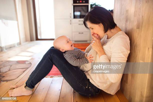 Mother at home with her baby sitting on the floor