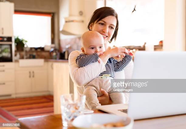 Mother at home with her baby working on laptop
