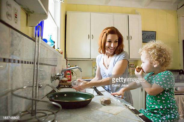Mother at sink smiling at child