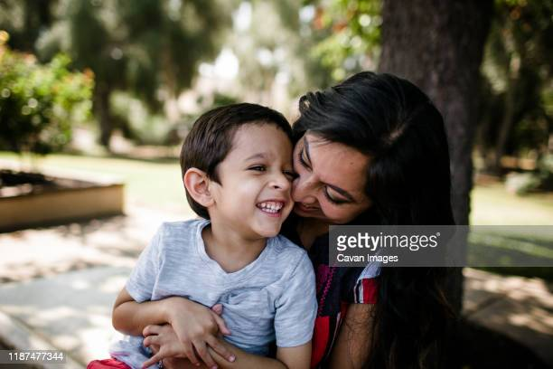 mother & autistic son laughing & hugging - autismo fotografías e imágenes de stock