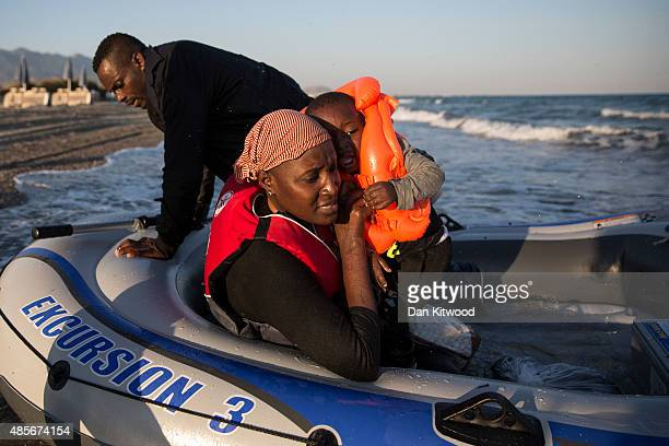 Mother Awa and son Mohammad from the Gambia arrive on a beach in an inflatable dinghy on August 29 2015 in Kos Greece Migrants from many parts of the...