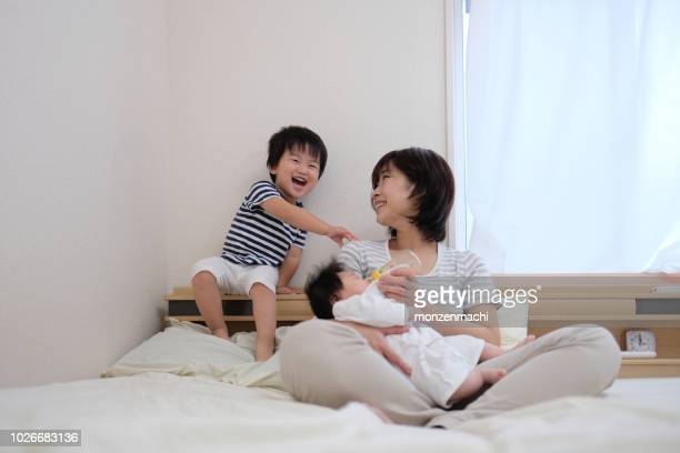 mother, baby and toddler sitting on the bed - japanese breastfeeding stock pictures, royalty-free photos & images