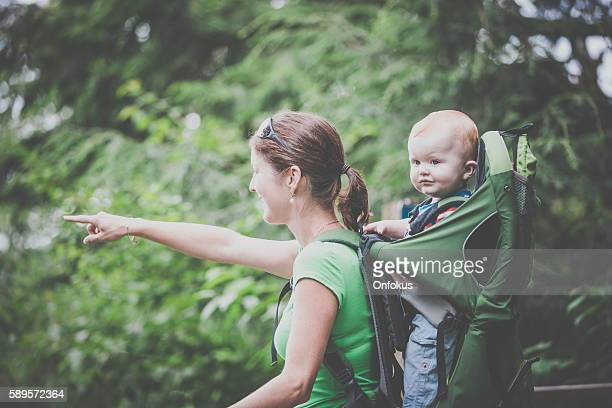 mother backpacking hiking with baby in forest - baby pointing stock photos and pictures
