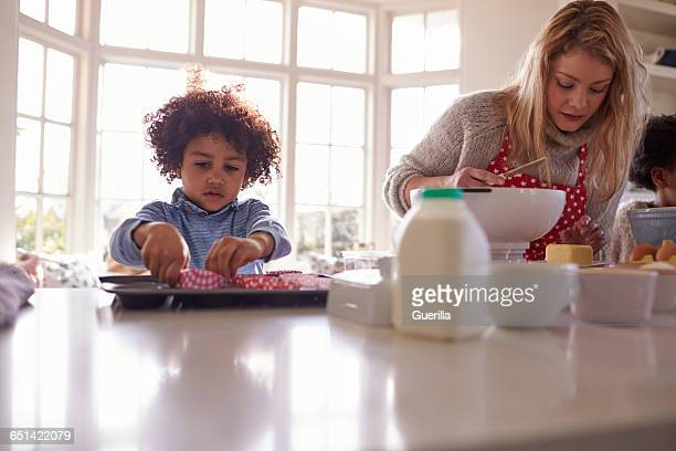 mother baking cake with children in kitchen at home - ウェスト・バークシャー ストックフォトと画像