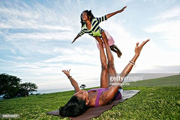 Mother balancing daughter on legs in park