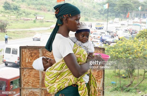 A mother begs with her twin babies in street in Abidjan in Ivory Coast on March 14 2017 / AFP PHOTO / ISSOUF SANOGO