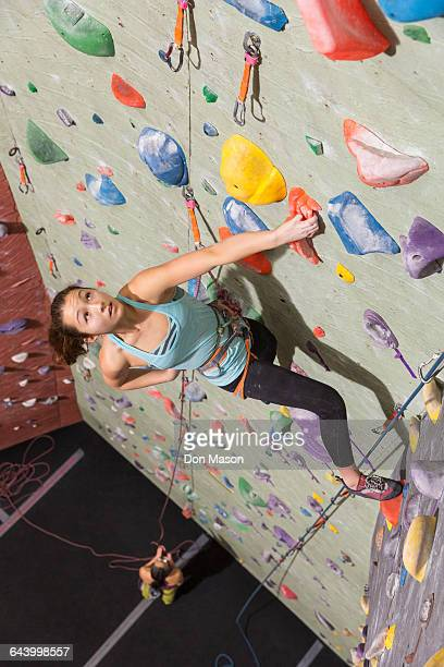 Mother belaying daughter climbing rock wall