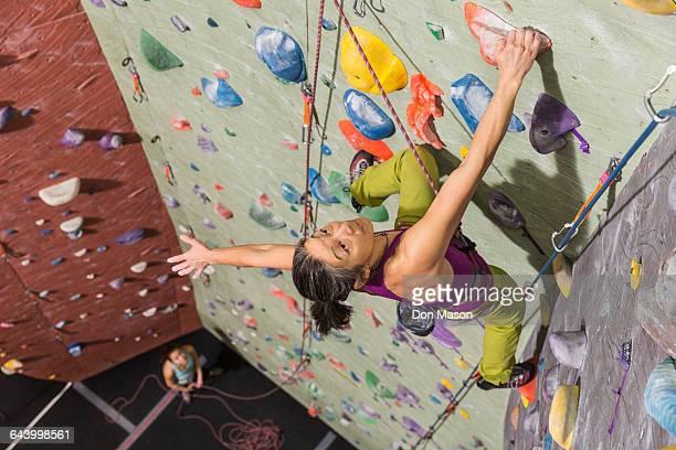 mother belaying daughter climbing rock wall - クライミングウォール ストックフォトと画像