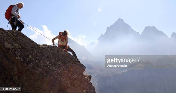mother belays daughter while climbing rock ridge, using rope - moving up stock pictures, royalty-free photos & images