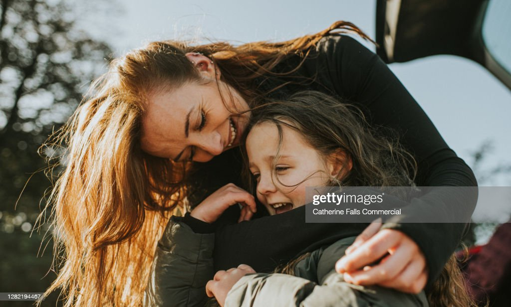 A mother bends down to embrace her daughter from behind : Stock Photo