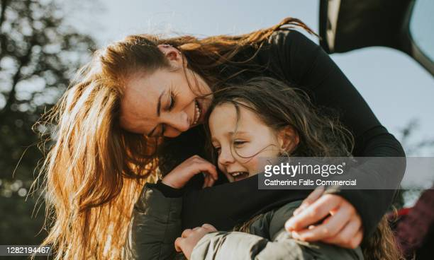 a mother bends down to embrace her daughter from behind - love stock pictures, royalty-free photos & images