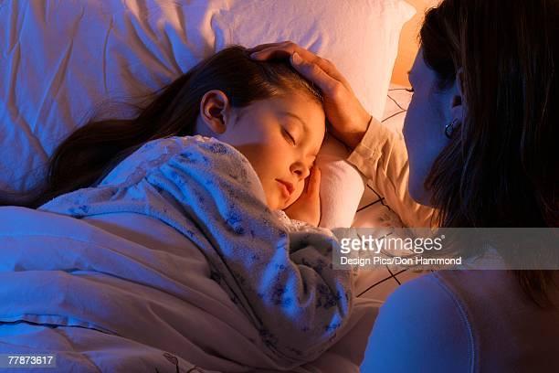 Mother beside sleeping daughter