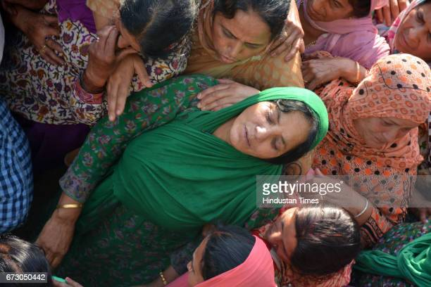 Mother Bimla with martyr CRPF jawan Surender Kumar's body at native village Ner Chowk before cremation on April 25 2017 in Mandi India