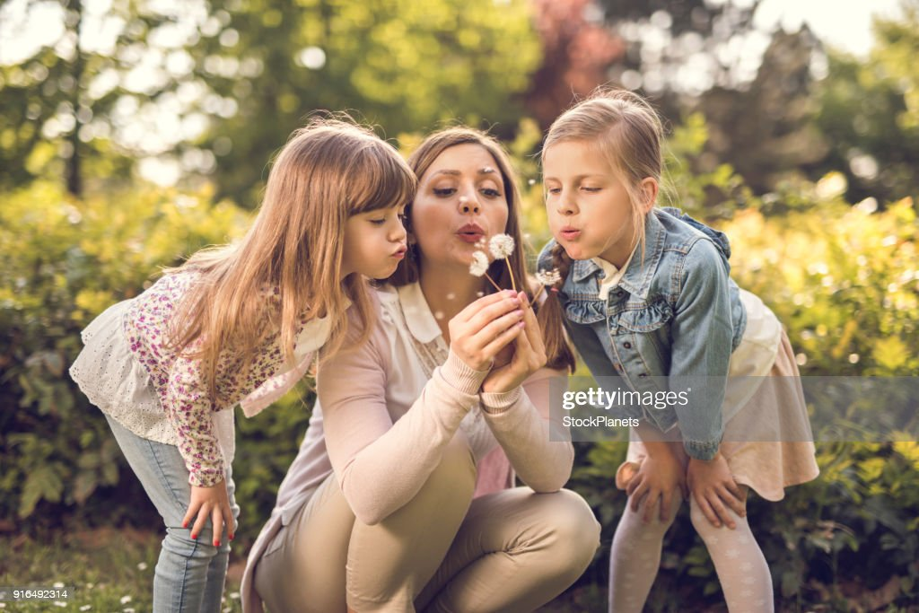Mother blowing at dandelion with two small daughters : Stock Photo