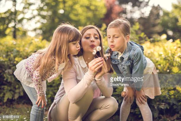 Mother blowing at dandelion with two small daughters