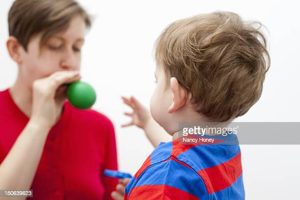 Mother blowing balloon for son