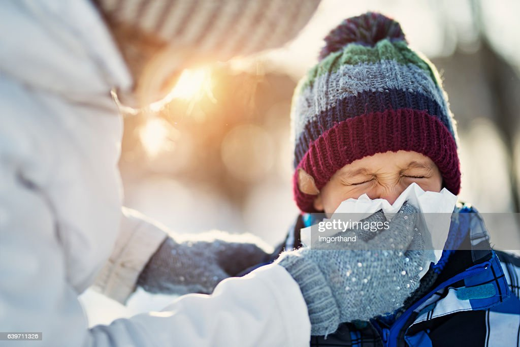 Mother blowing nose of her sick son during winter walk : Foto de stock