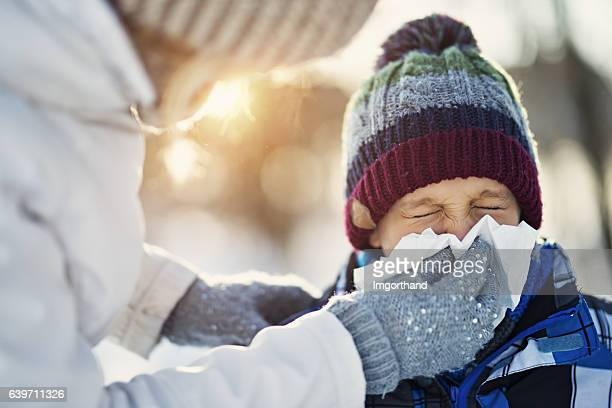 mother blowing nose of her sick son during winter walk - pneumonia stock pictures, royalty-free photos & images