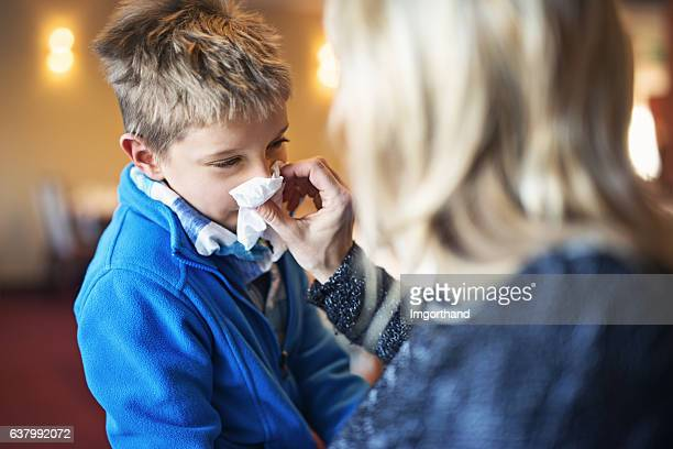 Mother blowing nose of her sick son