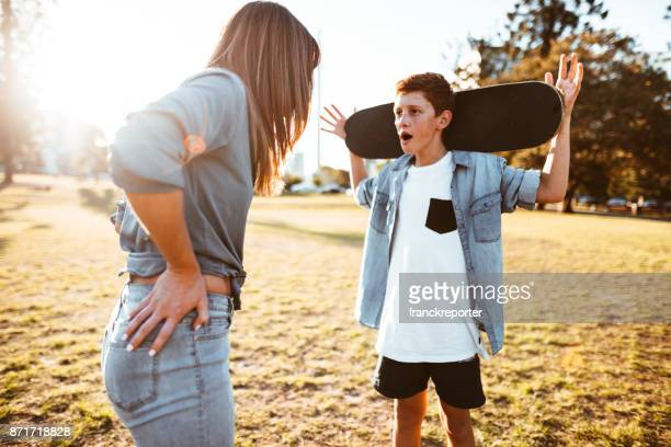 mother bothering the son with the skateboard - mother scolding stock pictures, royalty-free photos & images