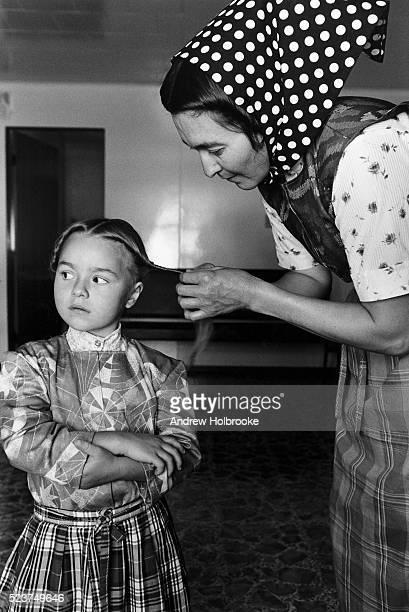 mother braiding daughter's hair - hutteriter bildbanksfoton och bilder