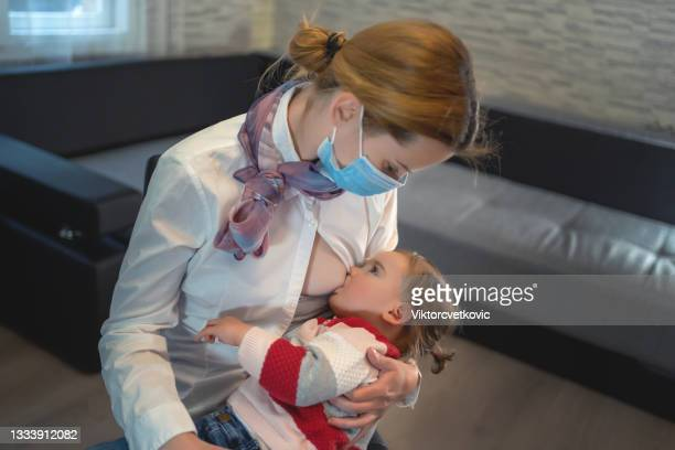mother breastfeeding child at home in isolation - audience free event stock pictures, royalty-free photos & images