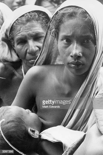 A mother breastfeeding her baby in crowded conditions at Salt Lake refugee camp Calcutta India after fleeing Pakistan during the secession of...