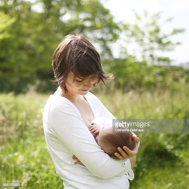 A mother breastfeeding her baby in the countryside